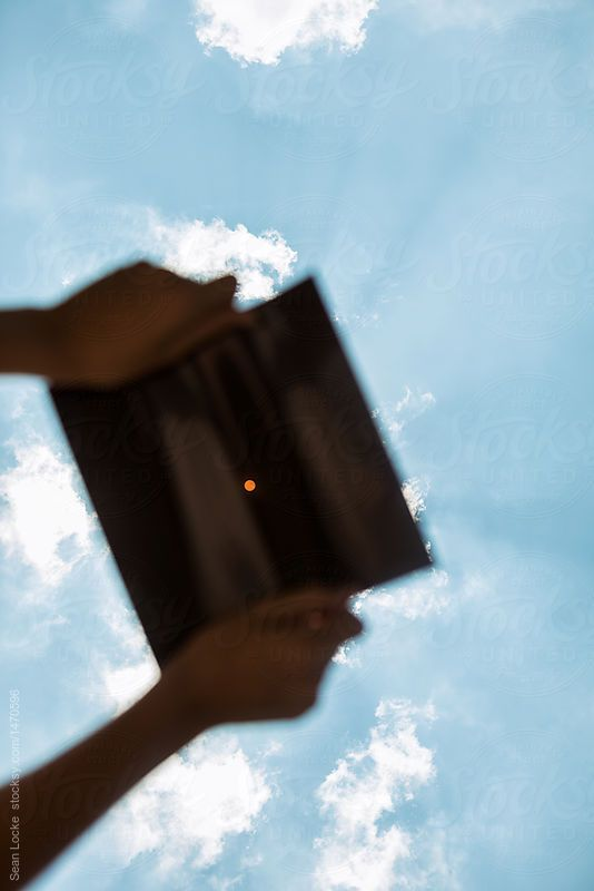 Eclipse: Sun Rays Beam As Girl Holds Filter Film And Looks At Sun by Sean Locke for Stocksy United