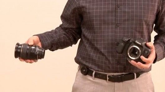 A device to aid two-handed humans in changing lenses on a DSLR