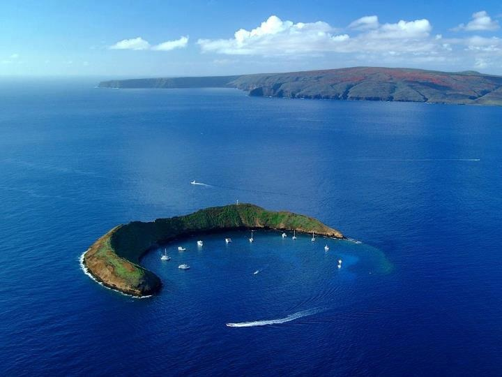 The Crescent-Shaped Molokini Crater in Hawaii Molokini is a small, crescent moon-shaped volcanic crater island that is a State Marine Life and Bird Conservation District. Just three miles from Maui's southwestern coast, it spans over 18 acres and rises 160 feet above reef-filled waters, offering visitors snorkeling and diving among a kaleidoscope of coral and more than 250 species of tropical fish. Photographer: Ron Garnett