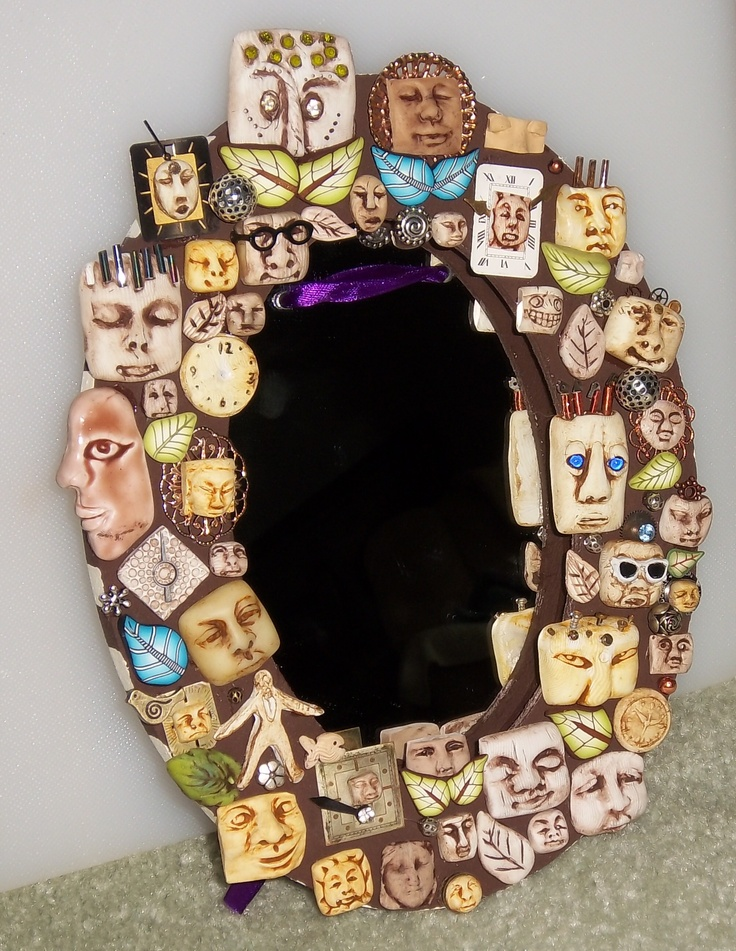 A face mirror. Polymer clay faces on a frame surrounding a mirror.