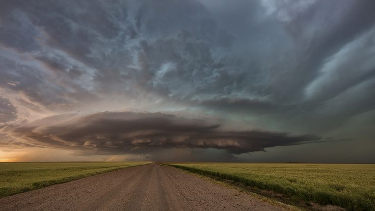 Beautiful and ominous tornado warned supercell thunderstorm over the Kansas wheat fields this year. I love how the road takes you right into the storm's core, where grapefruit sized hail and 90 mph winds await anyone foolish enough to enter it! Check out our storm chasing tours at www.silverliningtours.com !!!!!!!!!