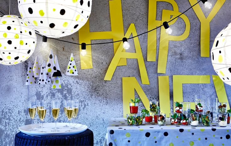 Ein Raum, der mit einem Punktethema für die Silvesterparty dekoriert wurde; auf einem Tisch stehen Menügänge in Gläsern und Sektgläser.
