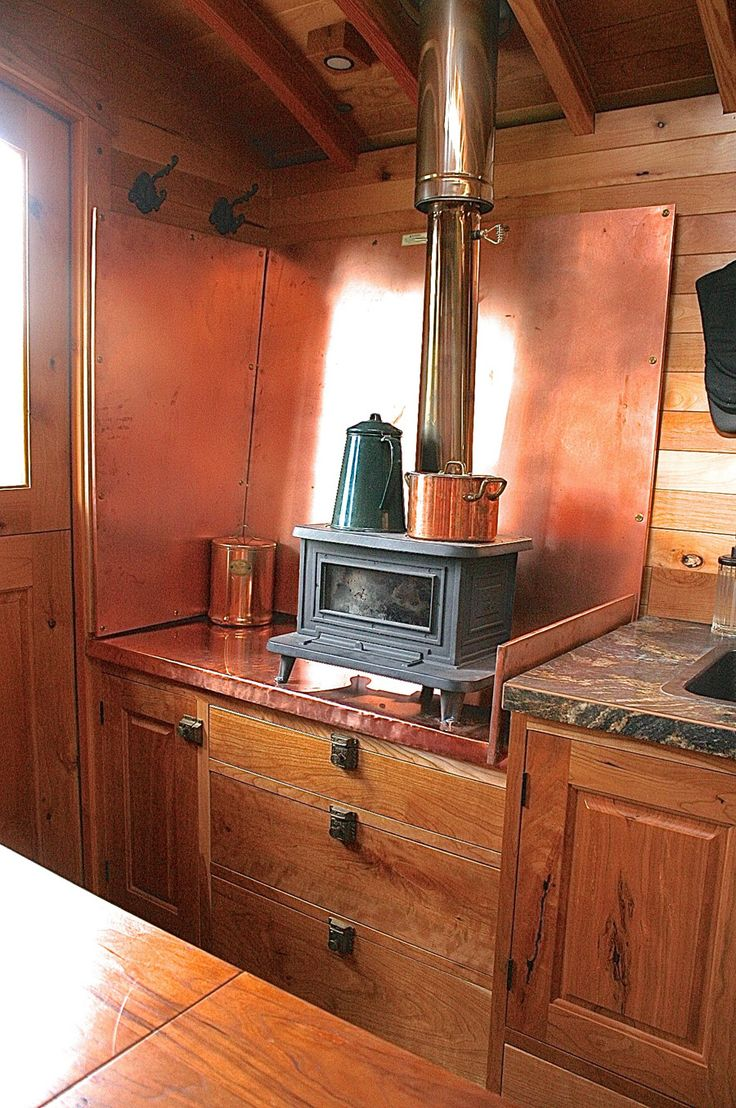 Marine wood-burning stove in this small kitchen. That copper back piece is pretty cool, too. | A tiny home in Plain, Washington. Owned and shared by Andrew Campbell. | Tiny Homes