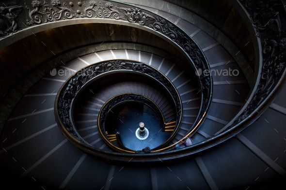 Long spiral, winding stairs. Dark shadows, soft light.