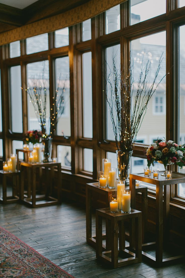 Indoor ceremony backdrop with lighted branches and candles