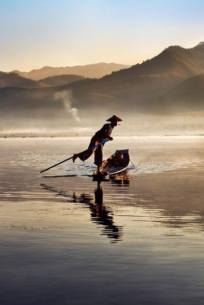 An Intha fisherman paddles his boat on Inle Lake in Burma/Myanmar. Some Intha people live at the edge of the lake, but others grow vegetables in floating gardens, and live in houses on stilts.