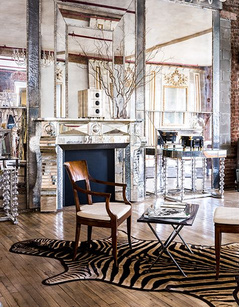 This mirror-paneled living room features a Serge Roche–inspired fireplace with antique watery mirrors around the hearth and silvered bull's-eye mirrors set in each corner and the center.