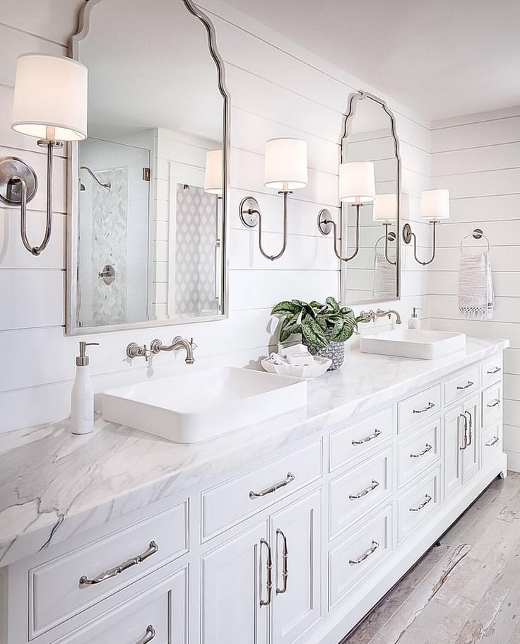 Shiplap bathroom wall with white cabinetry white marble countertop wall mount faucet and rustic looking floor tile
