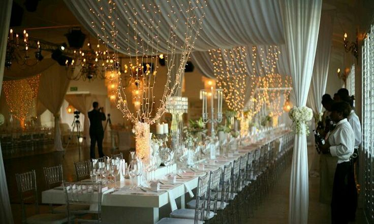 stunning wedding reception, white drapes, clear chiavari chairs on long table setting, fairy ...