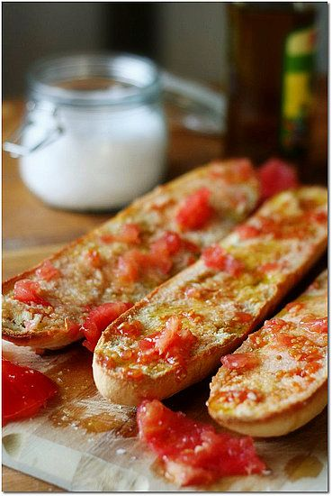 "Pa amb tomàquet. Literally in English: ""Bread with tomato"". It's a simple and typical recipe in Catalonia. It consists of bread —optionally toasted— with tomato rubbed over and seasoned with olive oil and salt. Sometimes garlic is rubbed on the bread before rubbing in the tomato."