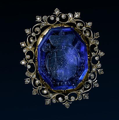 The Archbishop Johann Hugo von Orsbeck's Armorial Sapphire, 17th Century AD, Setting: 19th Century AD. Germany | Gold, silver, and diamond brooch, set with an octagonal sapphire engraved with the arms of Johann Hugo von Orsbeck (1634-1711), appointed Archbishop Prince Elector of Trier, 13 July, and Bishop of Speyer, 16 July 1676, Abbot of Prum and Provost of Weissenburg. Now framed within a foliate border.