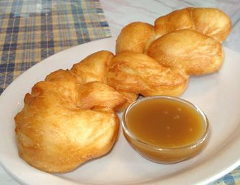Tresse is an Acadian dessert.    It is a yeast-raised bun.    The dough is pieces of plain bread dough, that are braided, then deep-fried to cook them.    It is served warm with a side dish of caramel sauce to dip pieces into.