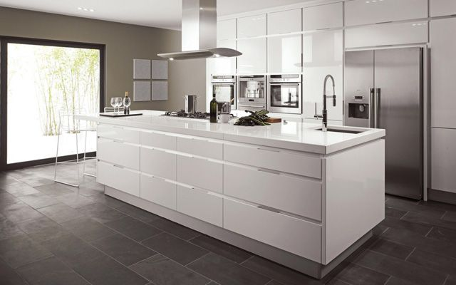 Central Breakfast bar in white with matching kitchen storage units and oven in this modern kitchen design