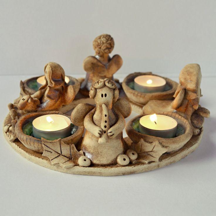 Adventní věnec I. Keramický adventní svícen se čtyřmi andílky. Průměr věnce je 22cm, výška andílků cca 8 cm. V miskách je roztavené zelené sklo. Tento svícen se hodí k umístění doprostřed stolu.