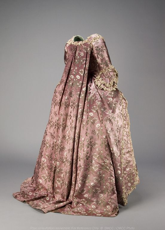 Rear view, robe à la francaise, England, c. 1760-1770. Pink-purple satin brocade with a pattern of floral sprays worked in white and green.