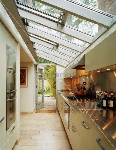 Glass roof above long kitchen counter with spotlights reflected in stainless steel worktop