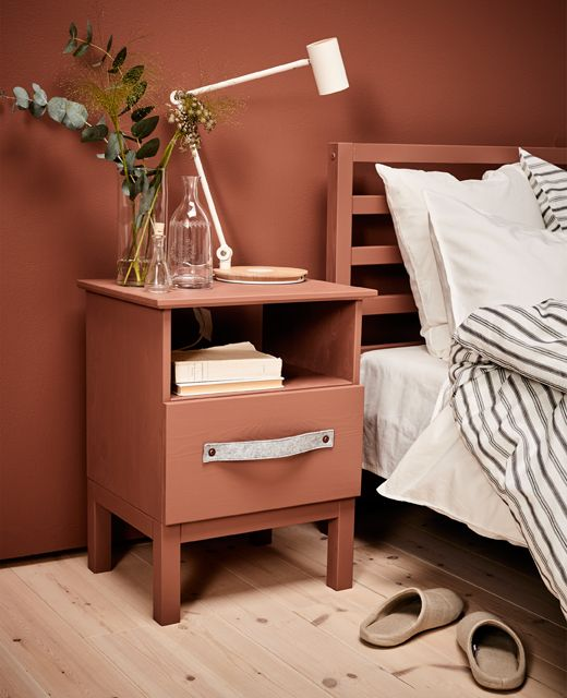 A made over bedside table sits next to a bed.