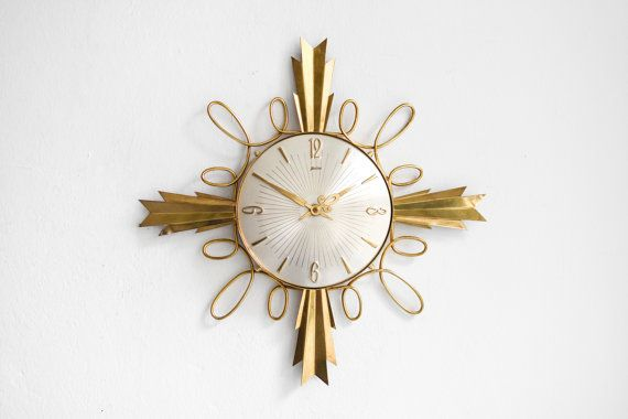 Large Palmtag clock 60s.  Look at you, you beauty! I love everything about this clock: the bold large brass rays, the delicate brass wire adornments, the matte silver clock face as an elegant counterweight to all the brass and the beautifully shaped hands. For sure this large clock from German maker Palmtag will be the center of attention in any room.  It reads Palmtag on the clock face and there is an original sticker on the back. It runs with a standard AA battery. The original clockwork…