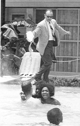U.S.A. June, 1964. Black children integrate the swimming pool of the Monson Motel. To force them out, the owner pours acid into the water.