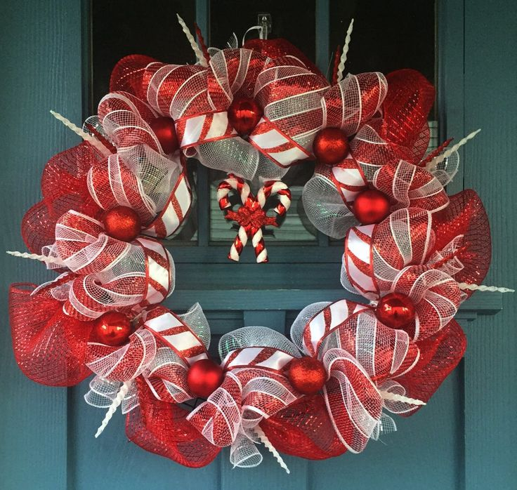"- Wire wreath frame covered with red and white mesh intertwined with ""candy…"