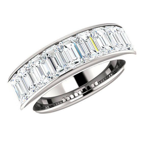 Canale impostato nella vostra scelta di solido oro bianco 14k, 18K o platino, questa band caratteristiche 5x3mm taglio smeraldo Supernova Moissanite gemme canale-set a metà strada intorno alla banda, con un peso totale di carati di 2,70 carati.  Per ulteriori anelli di fidanzamento, si prega di visitare il nostro sito Web: www.ravendiamonds.com   Dettagli:  Supernova Moissanite (viene fornito con certificato di autenticità) Forma: Taglio smeraldo Peso: 2,70 carati (0,30 ct ciascuno) Colore…