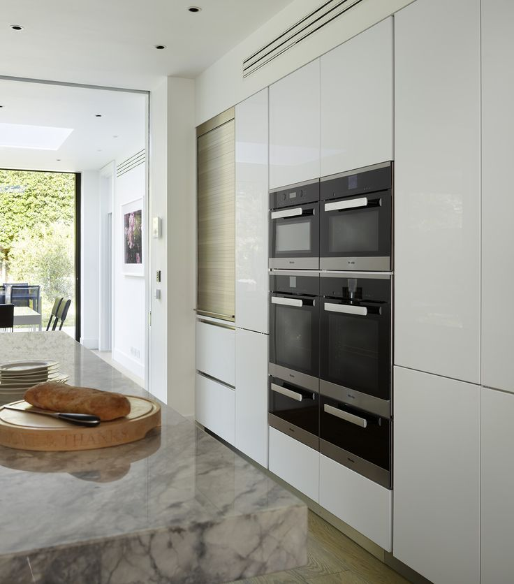 This contemporary, open plan kitchen was designed by Eve Turner of Neil Lerner Kitchen Designs, featuring minimalistic white handleless units to create a feel of space and light, whilst providing ample storage space