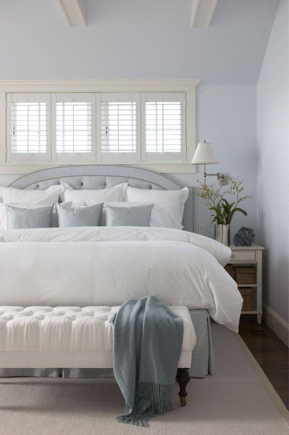 Small Bedroom looks larger due to the use of whites and grays.  This trick works well in most rooms.  Be careful, don't make a room look like a hospital.  The dark hardwoods peeking out around the edges of the rug adds warmth to this room.  Use a wall lamp instead to leave additional usable space on the nightstand.  Plantations shutters keep the room from looking weighed down.