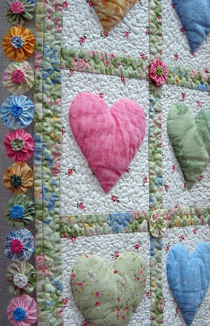 Just a photo. Pinning this for the idea.  I love the puffed hearts and the yo-yo appliques.  A very neat quilt.  :-)