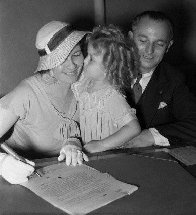 Shirley Temple and her parents sign to adjust the terms of Shirley's contract to the 20th Century Fox studio, 1934.