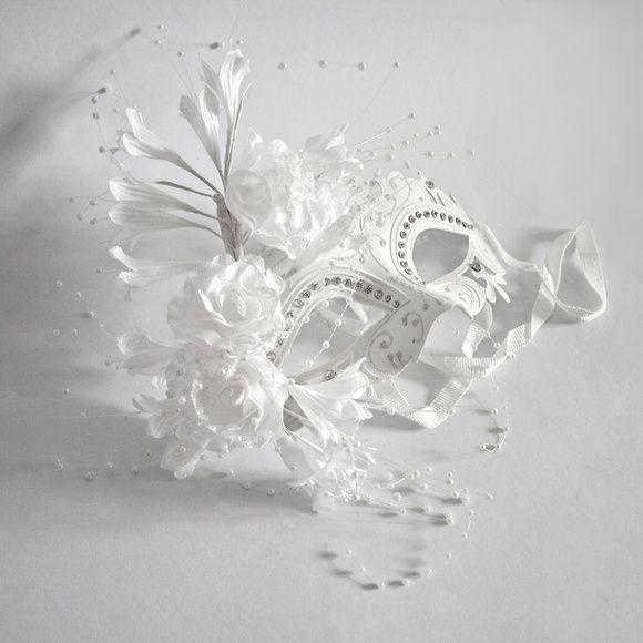 Máscara Serena Luxo    Máscara importada com pintura em glitter branco feita à mão e pedras de strass acopladas. Possui detalhe, na lateral direita, de flores de tecido branco com mini contas imitando pérolas,e cristal na parte superior central. Possui fita para amarrar na cabeça e embalagem espe...