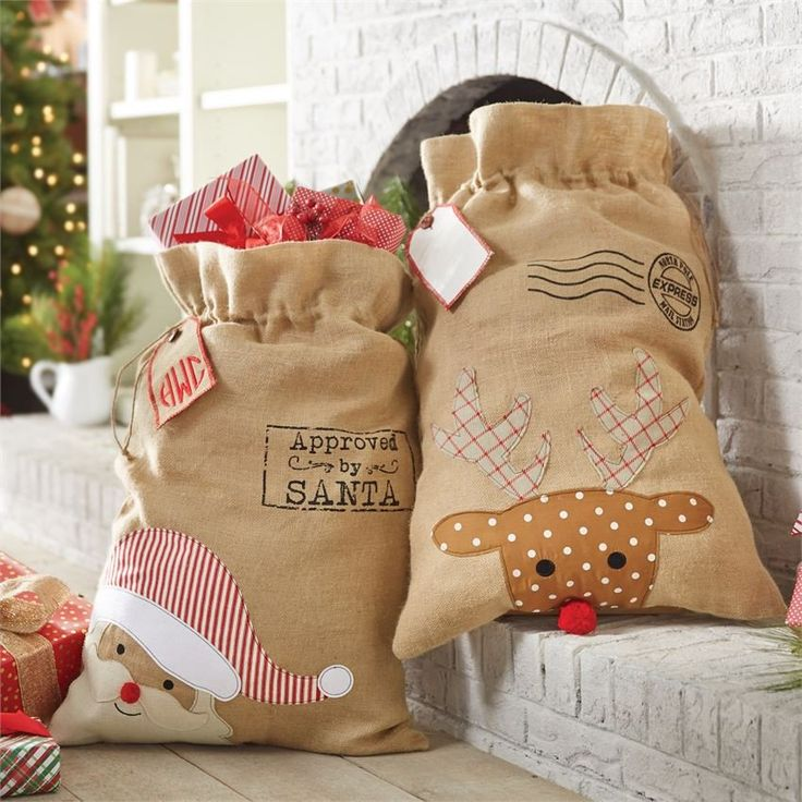 """""""Approved by Santa"""" and """"Reindeer Express"""" oversized reusable drawstring burlap sacks from Mud Pie feature Santa and reindeer appliques with pom-pom nose accents. Arrives with reversible vinyl burlap"""