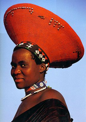 This ZULU BRIDE wears a flaring red HEADDRESS reminiscent of the hairstyle of her ancestors. TRADITIONALLY, this headdress was made of her mother's hair.