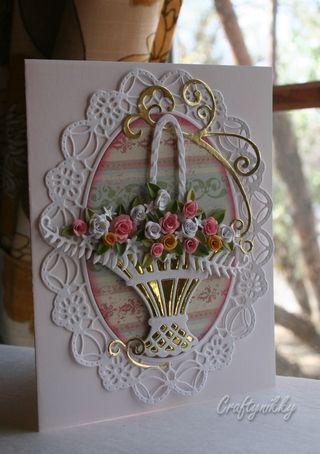 """Uses IO's rolled flowers dies for this card. I have a similar basket die from Marianne Designs. Lovely how she used gold foil paper behind the basket to add """"bling""""."""
