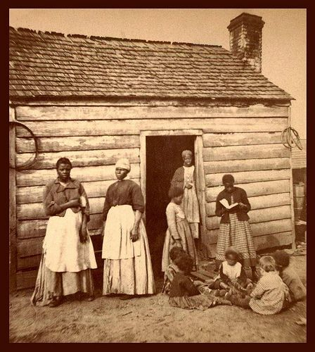 """SLAVES, EX-SLAVES, and CHILDREN OF SLAVES IN THE AMERICAN SOUTH, 1860 -1900 (2) -- And one WHITE KID with Back to the Camera    """"Aunt Betsey's Cabin"""" in South Carolina."""