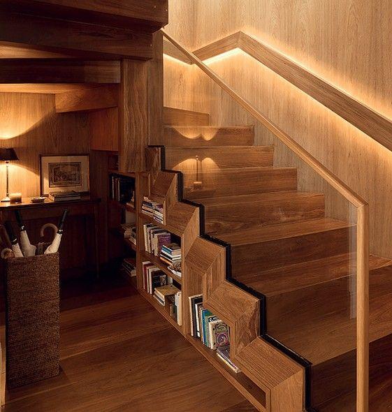 A escada de madeira maciça ipê que dá acesso à cobertura deste duplex ganhou mais uma função no projeto da arquiteta Marina Linhares. Ela criou uma estante para guardar livros na área ociosa embaixo dos degraus