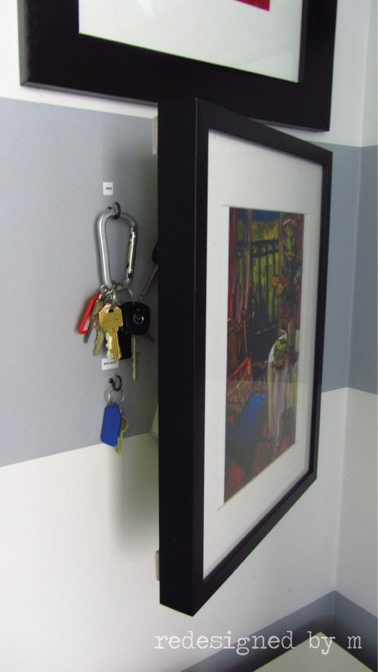 hidden key holder picture frame mounted on an entryway wall