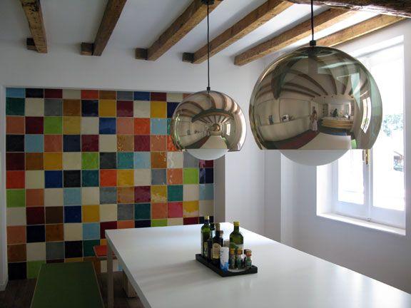 Cucina multicolor. La parete è stata decorata con delle piastrelle di cotto lavico da 10 x 10 cm.