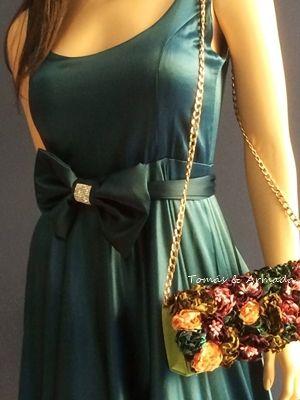 Bolso de fiesta con flores multicolor sobre un vestido verde.