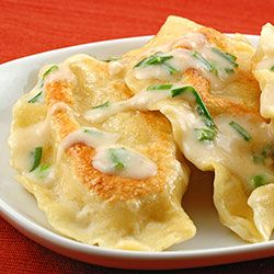 Homemade Potato-Cheese Pierogi with Sour Cream Garlic-Chive Sauce! This sounds so good!