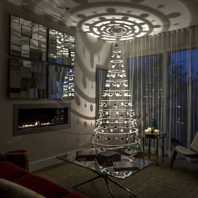 Update your holiday decor with the innovative and unique Modern Christmas Tree, created by Matthew Bliss. Lights and shadows dance on to    walls and ceiling, while a battery powered mirror ball rotating device casts reflections throughout the room.                Made of durable and lightweight acrylic                    Easy to set up                    9-watt, 110 volt LED spotlight                    Glass ornaments, chandelier crystals                    Comes with an LED light, mir...