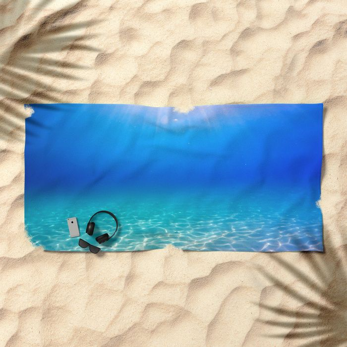Underwater picture taken in Greece on a beautiful sandbeach with crystal clear water and the sun rays shining through the surface, creating a display of glowing patterns on the bottom. #underwater #water #sea #ocean #beach #summer #travel #adventure #blue #swimming #freediving #diving #towel #beachtowel