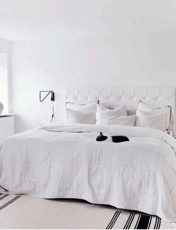 Bright white bedroom with white tufted headboard and black wall sconce