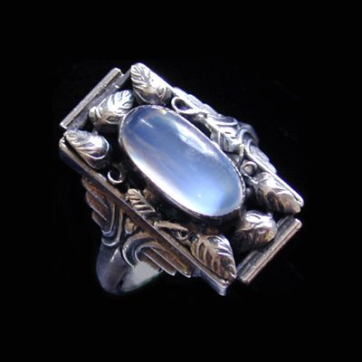 This is not contemporary - image from a gallery of vintage and/or antique objects. ARTS & CRAFTS  An Arts & Crafts silver ring set with a moonstone, surrounded by leaves and wirework stems.