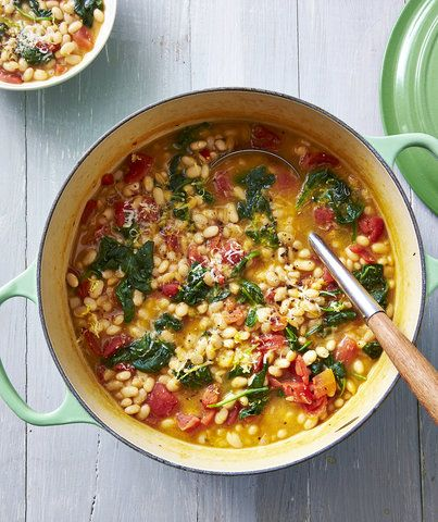 White Bean-and-Parmesan Soup | Dip your ladle into this recipe for a taste of Northern Italy. Dried white beans get cooked with vegetable stock, Parmesan cheese rinds, and onion halves. The Parmesan rind flavor really comes through in the finished soup, and the tomatoes, lemon zest, and baby spinach which get stirred in later give the umami-rich beans a nice pop of brightness. (=)
