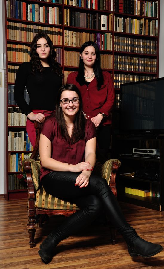three young ladies in front of a bookshelf - family