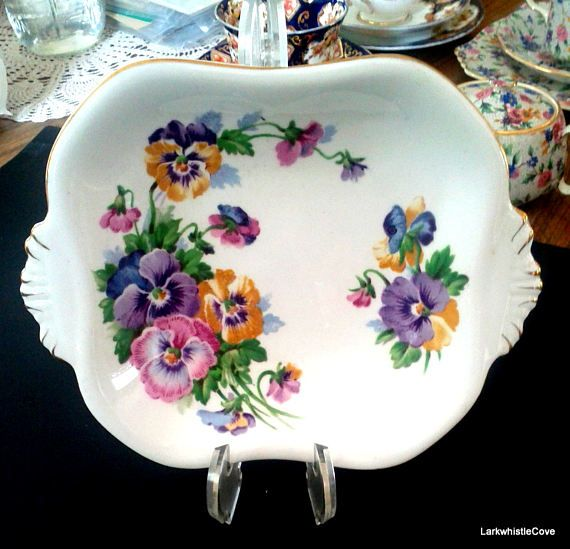 Queen Anne Spring Melody Pansy Pattern Double Handled Serving Dish or Cake Plate Fine Bone China Made in England Lovely purple, pink and yellow pansy pattern Gold trim on the rims and scalloped handles 7 3/8 handle to handle 5 7/8 side to side 1 1/4 tall Mint condition!  Combined shipping is available and up to 3 teacups sets or other small items can be mailed for the same cost as shipping 1 set. Thanks for stopping by