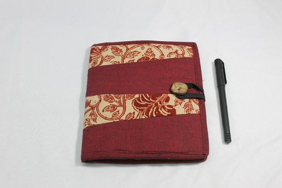 A diary with a kalamkari and dark pink cotton cover, with a pocket inside, as well as a tasselled bookmark stitched by hand