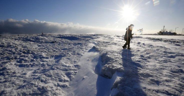 Mulheres caminham ao longo de uma praia congelada no lago Michigan, em Chicago, nos USA.  Fotografia: Jim Young/Reuters.