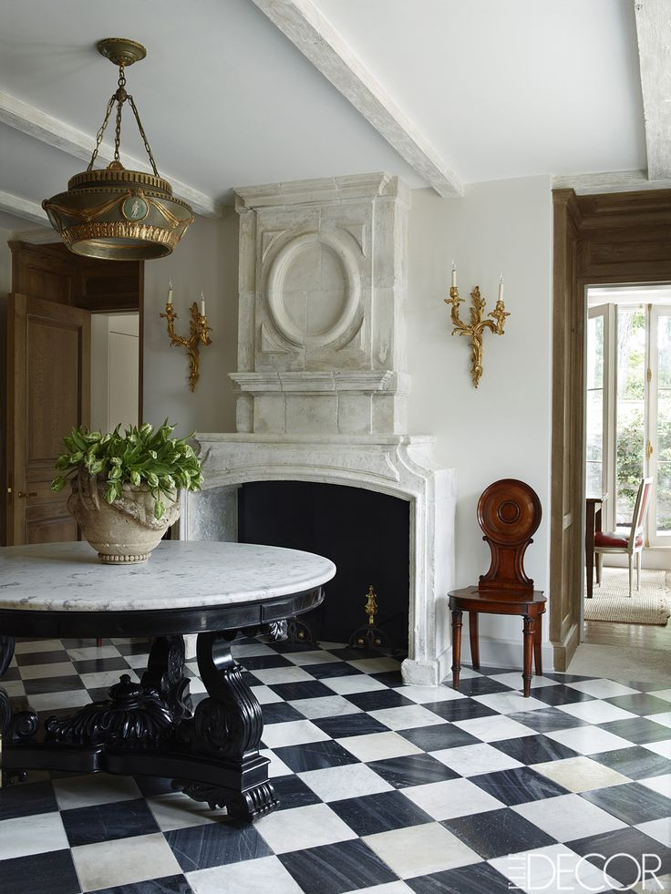The front hall's Indian table and English chandelier and chair are 19th-century, and the 17th-century fire- place is limestone; the marble flooring is by Exquisite Surfaces.   - ELLEDecor.com