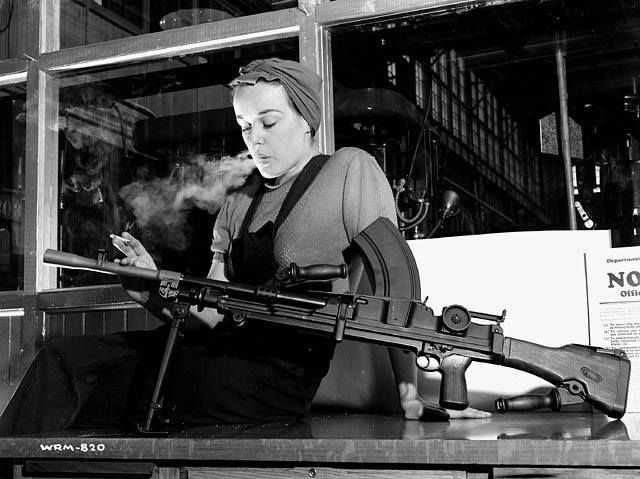 """Veronica Foster, an employee of John Inglis Co. Ltd. and known as """"Ronnie, the Bren Gun Girl"""" posing with a finished Bren gun in the John Inglis Co. Ltd. Bren gun plant, Toronto, Ontario, Canada. 10th May 1941. (Library and Archives Canada)"""